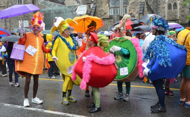 A group of men dressed up as different fruits, banana, kiwi, blueberry, apple and orange