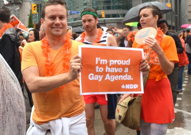 "people at a pride parade in the rain - a man in an orange Tshirt holding a sign that says ""I'm proud to have a gay agenda, NDP"""