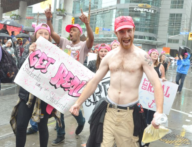 "people at a pride parade in the rain - a topless man in a pink hat who is helping to hold a sign that says ""Get Real""  Others around him are also wearing pink hats"