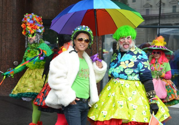 people at a pride parade on a rainy day - a group of four men in colourful and outrageous drag stop to pose for a photo