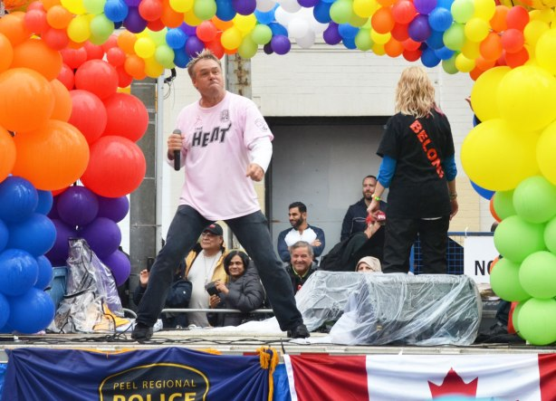 people at a pride parade in the rain - a man dancing and holding a mic, with a funny look on his face, on a float from the Peel Regional Police, called the Heat,  there are lots of balloons beside and above him.