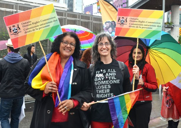 people at a pride parade in the rain - some women holding signs promoting the Human RIghts Commission.  they are holding rainbow flags as well