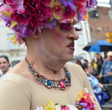 people at a pride parade on a rainy day - an older man in a flowery wig and flowery top along with a bulky necklace stands in front of a crowd, close up shot of head and shoulders