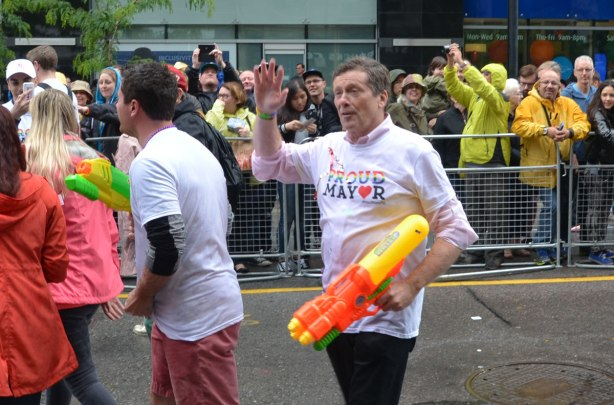 people at a pride parade on a rainy day - Toronto mayor John Tory walks in the parade while holding a large yellow and orange super soaker