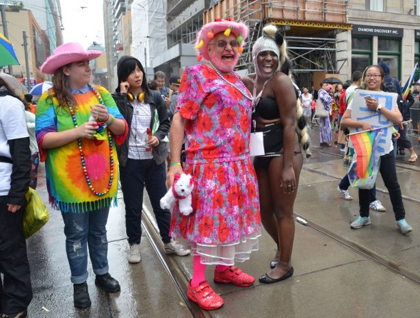 people at a pride parade on a rainy day - a man in drag - long pink dress, pink socks and pink shoes laughs while posing for a picture with a large black person in skimpy costume who is also laughing