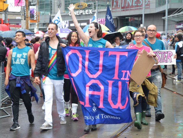 A group from the University of Toronto marches in a pride parade.  They have a large blue banner with pink lettering that says Out in Law.