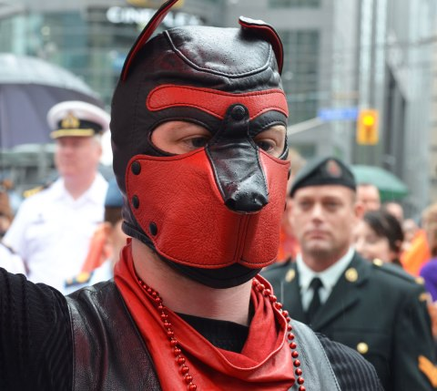 people at a pride parade in the rain - close up of a man in a red and black leather mask that covers his whole head, behind him and slightly blurry are two soldiers, navy guy in white on one side and army guy in greenish uniform on the other side