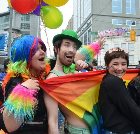 people at a pride parade on a rainy day - three people pose for a photo.  One in a multicoloured wig, one with a green hat and one with flowers in her hair