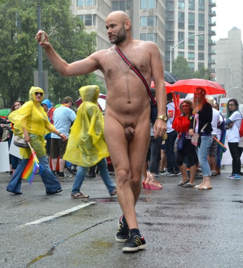 people at a pride parade on a rainy day - a nude man poses in the middle of the road while he takes a selfie.  Onlookers watch.