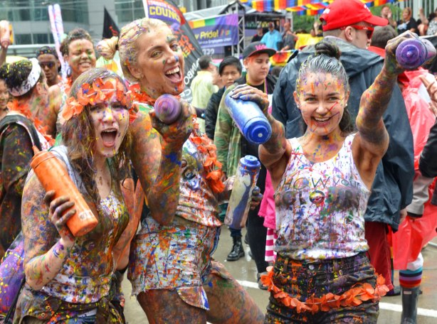 people at a pride parade in the rain - three young women holding squeeze bottles of paint, they are covered with paint that they have squeezed onto themselves
