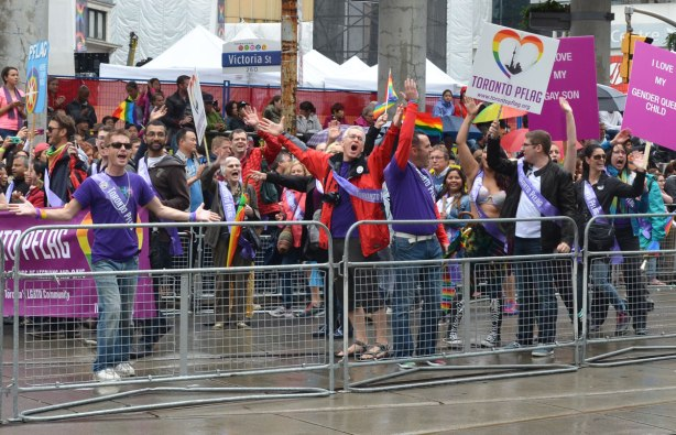 A crowd of marchers cheer -  people at a pride parade on a rainy day -