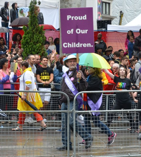 "people at a pride parade on a rainy day -  a man is holding a purple sign that says ""Proud of Our children"""