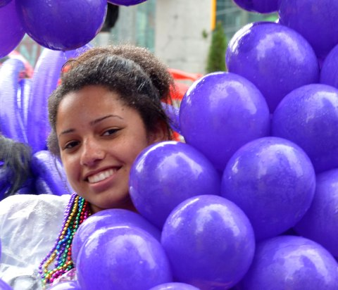 people at a pride parade in the rain - a young woman smiling from behind a lot of balloons that she is holding.