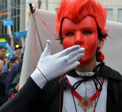 people at a pride parade on a rainy day - man is red mask and red wig as well as white gloves has his hand over his mouth as he begins to throw a kiss towards the camera
