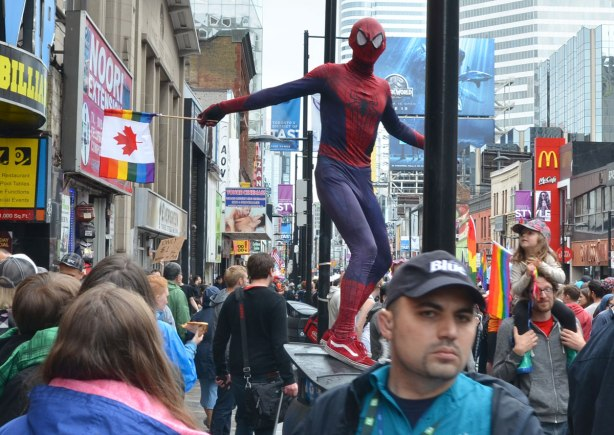 people at a pride parade on a rainy day - a man in a spiderman costume stands on a garbage bin so he is above the crowd on a sidewalk watching the parade
