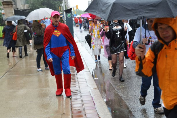 people at a pride parade in the rain - an older man in a superman costume walks along a sidewalk past other people who are walking on the road in preparations for the parade.  Most of them are holding umbrellas