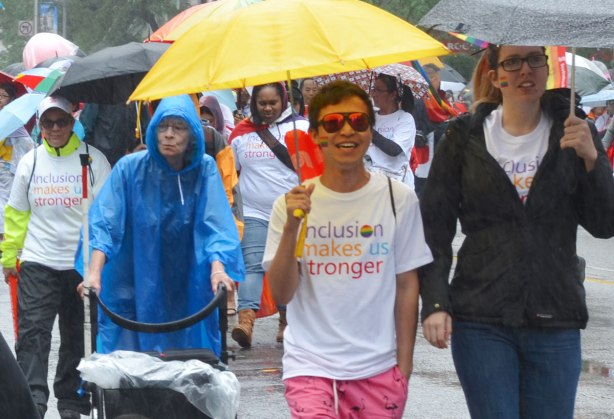 people at a pride parade in the rain