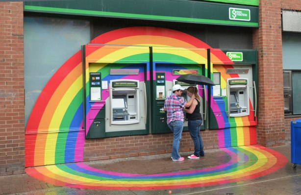 A couple is at an ATM on the side of the TD Canada Trust bank.  A large rainbow has been painted around it for pride week.