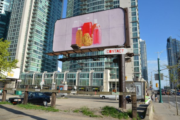 a billboard with a large picture of clear bottles filled with coloured liquids in reds and oranges.
