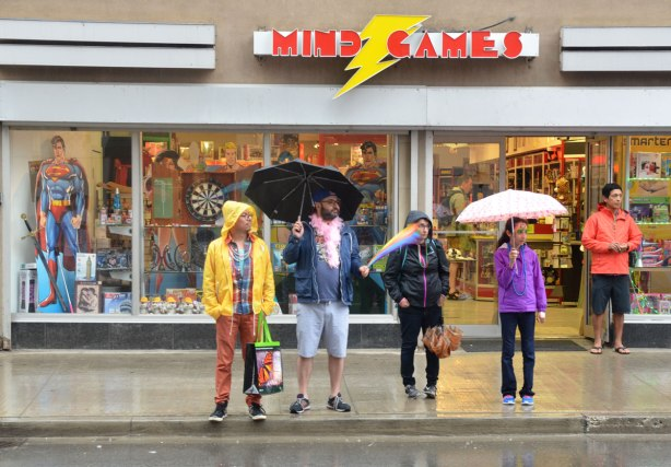 A group of people standing on a sidewalk in the rain as they watch a parade.   They are standing in front of a Mind Games store .
