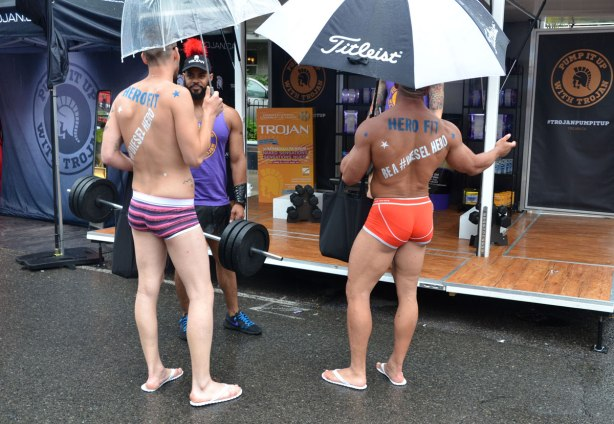 "Rear view of two well built men who are wearing just their briefs.  they have words painted on their backs, ""Hero fit"" and ""be a #diesel hero"".  They are standing in front of a Trojan booth, pride week display."