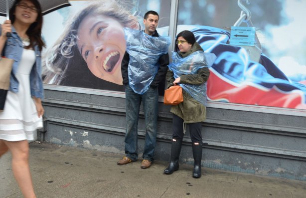 A couple in blue garbage bags as rainwear are standing in front of a billboard on which there is a picture of a woman.