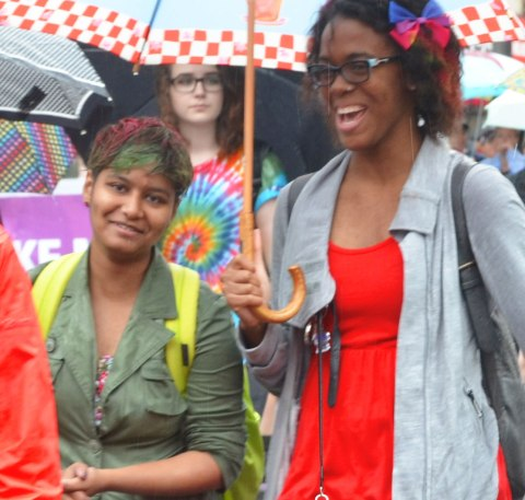 Two women, both smiling.  One is holding an umbrella and has a bow in her hair.  The other is also under the umbrella.