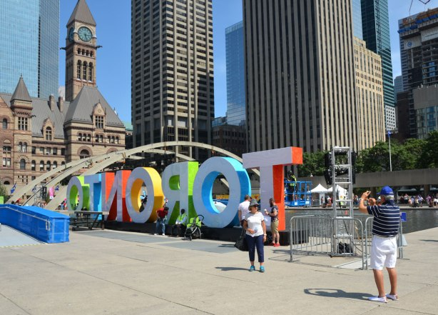 large three dimensional block capital letters that spell Toronto installed alongside the pool fountain in Nathan Phillips Square - from the back, Toronto is spelled in reverse but there are still people taking their picture by it