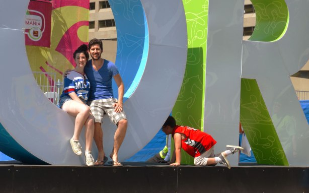 large three dimensional block capital letters that spell Toronto installed alongside the pool fountain in Nathan Phillips Square -  a couple sits in the O posing for a picture while a young boy crawls between the O and the R