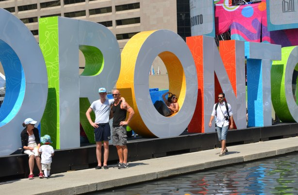 large three dimensional block capital letters that spell Toronto installed alongside the pool fountain in Nathan Phillips Square -  a couple stands in front of it, a man with a camera walks past it
