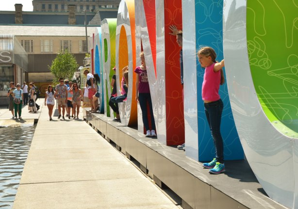 large three dimensional block capital letters that spell Toronto installed alongside the pool fountain in Nathan Phillips Square - kids standing in between the letters as well as in the round part of the O