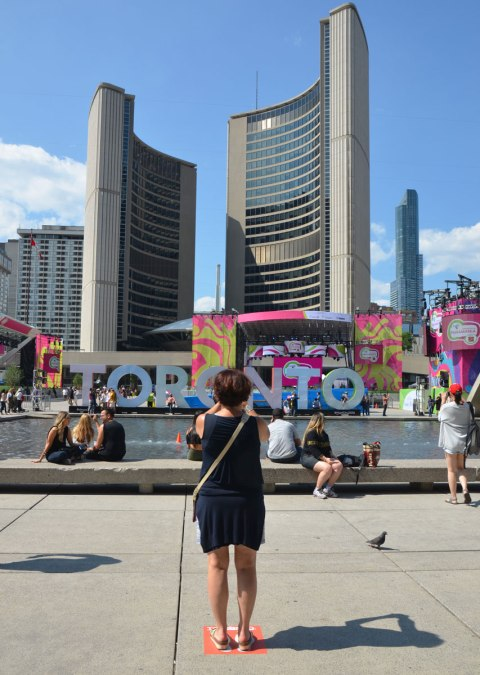 large three dimensional block capital letters that spell Toronto installed alongside the pool fountain in Nathan Phillips Square - a woman stands with her back to the camera and takes a picture