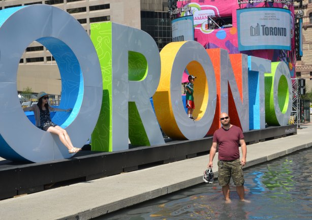 large three dimensional block capital letters that spell Toronto installed alongside the pool fountain in Nathan Phillips Square - a man stands in the water in front of the word Toronto