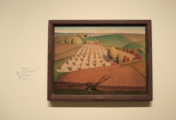 painting on a wall in an art gallery of fields being harvested by Grant Wood