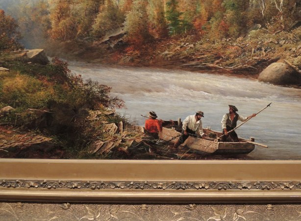 close up of part of a painting including part of the intricately carved frame.  THree men getting into a boat at the edge of a river