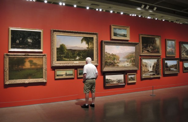 A man is looking at a wall of paintings. The wall is painted red. It is in an art gallery
