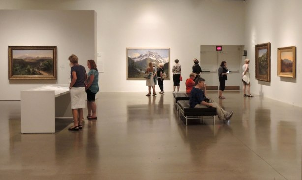 7 or 8 people in an art gallery looking at paintings that are hanging on the walls