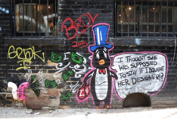 graffiti and street art in Graffiti Alley in Toronto - BRDL, Penguin looking worried, dollar bills are flying out of his pockets and into a (real) vent of the building.  He's wearing a blue tophat.  Word bubble says