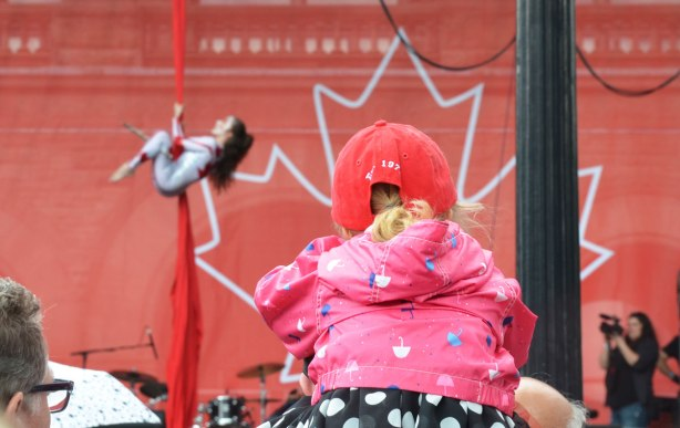 The back of a young girl wearing a red baseball cap and sitting on someone's shoulder as she watches an acrobat show on a stage