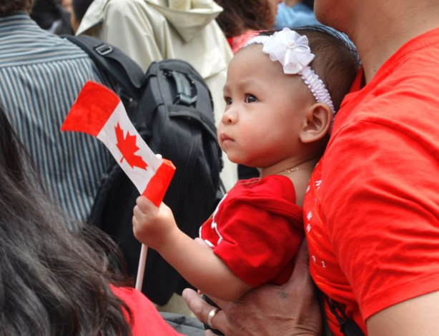 A young toddler wearing a white flower head band and a red T-shirt, and holding a Canadian flag is being held by her father