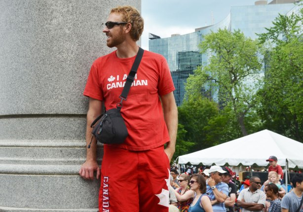 a red headed young man is standing on the base of a statue to get a better look at a show, the crowd is in the background.  He is all dressed in red and his Tshirt has the words I am Canadian on it