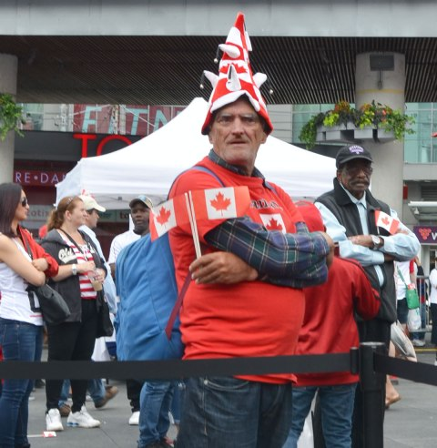 An older man in a red T shirt and a funny red and white hat is holding 2 small Canadian flags