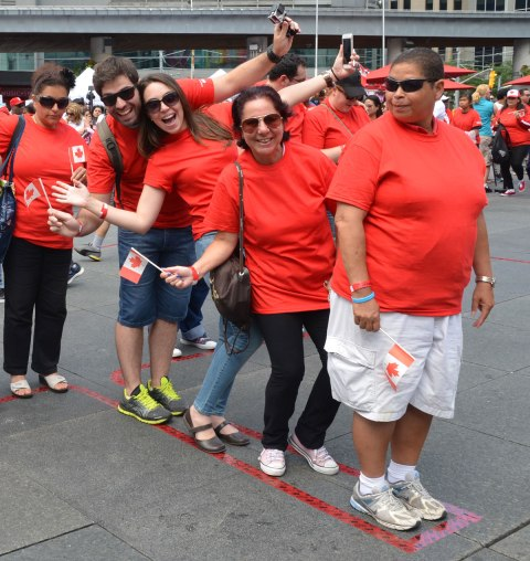 Five people pose for a photo.  They are wearing red T shirts and they are standing withing the stem of the maple leaf outline that is taped to the ground.  They are the first ones into the living flag that is trying to be made at Dundas Square as part of a Canada Day celebration