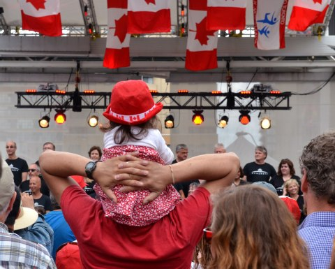 A man holds a young girl on his shoulders while the watch a performance of New Choir, a choir that sings old rock songs, as part of a Canada Day celebration at Dundas Square.  The girl is wearing a red hat with white maple leafs on it.  There are Canadian flags hanging from the ceiling of the stage.