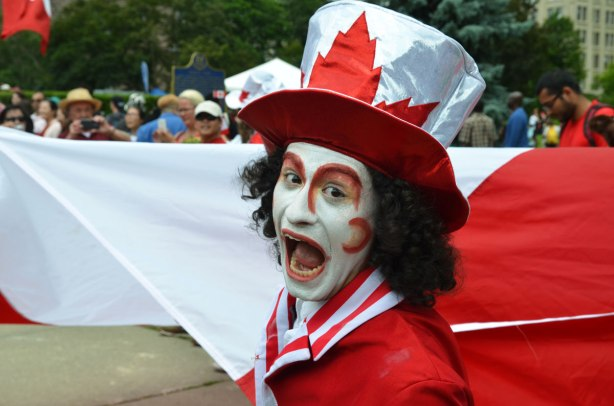 A man is hamming it up for the camera.  He is wearing a silver and red oversized tophat and a red and white costume.  He is holding the corner of a large Canadian flag
