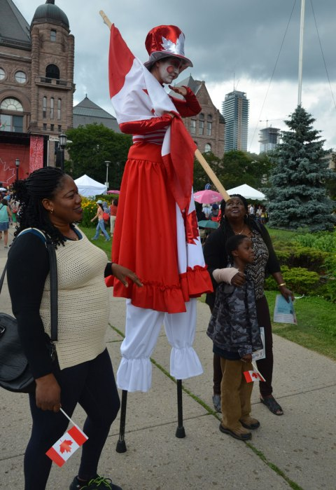 A person in red and white Canada Day costume is on stilts with three others standing beside, in front of the parliament buildings at Queens Park