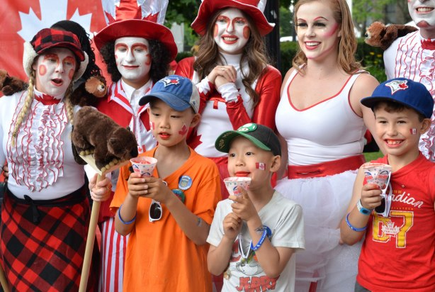 A group of characters in red and white Canada Day costumes stop to pose with some boys.  One of the characters has a stuffed beaver that is trying to take a sip of the boy's snowcone.