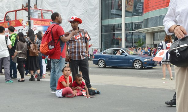 Two kids sit on the sidewalk beside two men who are talking.  Yonge Street is in the background, with traffic, including an open topped double decker bus.