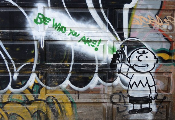 graffiti and street art in Graffiti Alley in Toronto - Charlie Brown in the bottom right corner of a garage.  In green are the words Be WHo You Are