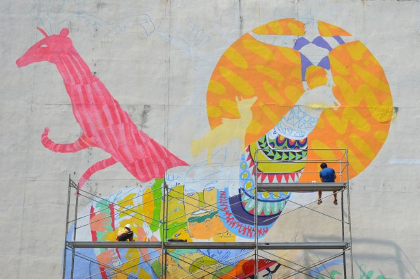 Two people sitting on scaffolding while they paint a mural